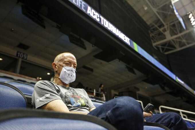 Mike Lemcke, from Richmond, Va., sits in an empty Greensboro Coliseum after the NCAA college basketball games were cancelled at the Atlantic Coast Conference tournament in Greensboro, N.C., Thursday, March 12, 2020. The biggest conferences in college sports all canceled their basketball tournaments because of the new coronavirus, seemingly putting the NCAA Tournament in doubt. The vast majority of people recover from the new coronavirus. According to the World Health Organization, most people recover in about two to six weeks, depending on the severity of the illness.  (Khadejeh Nikouyeh/News & Record via AP)
