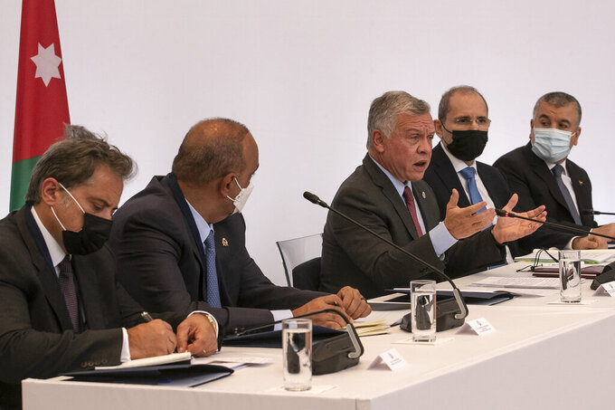 Jordan's King Abdullah II, center, speaks during a meeting in Athens, on Wednesday, July 28, 2021.  Greece is hosting a one-day trilateral meeting of the three leaders. (AP Photo/Yorgos Karahalis)