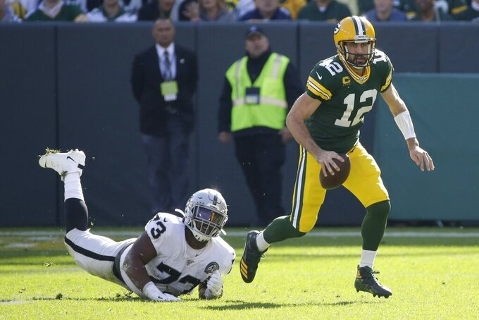 Green Bay Packers' Aaron Rodgers gets away from Oakland Raiders' Maurice Hurst during the first half of an NFL football game Sunday, Oct. 20, 2019, in Green Bay, Wis. (AP Photo/Mike Roemer)