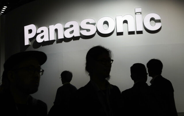 FILE -In this Jan. 9, 2018, file photo, people walk by the Panasonic booth during CES International in Las Vegas. Japanese electronics manufacturer Panasonic Corp. is abandoning the semiconductor business with the sale of its last business in that sector to a Taiwanese company. Panasonic said Thursday it was transferring the semiconductor business operated by Panasonic Semiconductor Solutions Co. to Nuvoton Technology Corp. (AP Photo/John Locher)