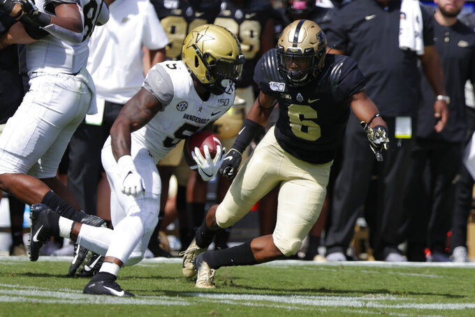 Vanderbilt running back Ke'Shawn Vaughn (5) cuts away from Purdue safety Jalen Graham (6) during the first half of an NCAA college football game in West Lafayette, Ind., Saturday, Sept. 7, 2019. (AP Photo/Michael Conroy)