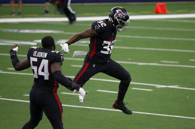 Atlanta Falcons' Foeysade Oluokun (54) and Jaylinn Hawkins (32) celebrate after making a stop on a fake punt attempt by the Dallas Cowboys in the second half of an NFL football game in Arlington, Texas, Sunday, Sept. 20, 2020. (AP Photo/Michael Ainsworth)