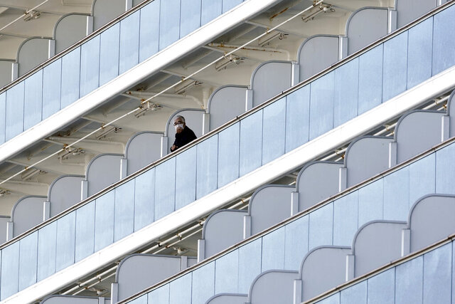 A passenger stand outside on the balcony of the cruise ship Diamond Princess anchored at the Yokohama Port Thursday, Feb. 6, 2020, in Yokohama, near Tokyo. The 3,700 people on board faced a two-week quarantine in their cabins. Health workers said 10 more people from the Diamond Princess were confirmed sickened with the virus, in addition to 10 others who tested positive on Wednesday. The 10 will be dropped off as the ship docks and transferred to nearby hospitals for further test and treatment. (AP Photo/Eugene Hoshiko)