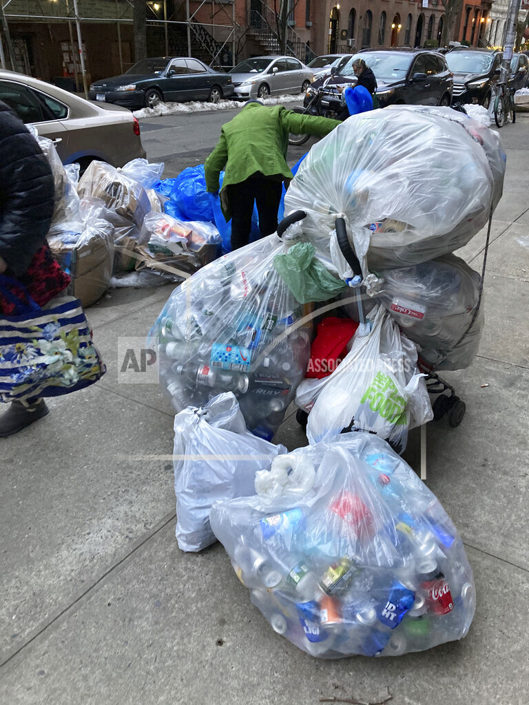 A woman collects recyclables during hard financial times in NYC