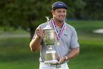 Bryson DeChambeau, of the United States, holds up the winner's trophy after winning US Open Golf Championship, Sunday, Sept. 20, 2020, in Mamaroneck, N.Y. (AP Photo/John Minchillo)