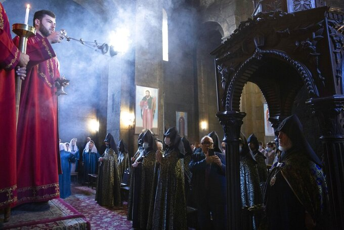 An Armenian Church priest conducts a service of remembrance for those killed in a war over the Nagorno-Karabakh region, at the Armenian Apostolic Cathedral in Etchmiadzin, the seat of the Oriental Orthodox church outside Yerevan, Armenia, Monday, Sept. 27, 2021. Azerbaijan and Armenia are marking the first anniversary of the start of their six-week war in which more than 6,600 people died and that ended with Azerbaijan regaining control of large swaths of territory. In Yerevan, the Armenian capital, thousands of people went to the Yerablur military cemetery to pay respects to soldiers buried there. (Grigor Yepremyan/PAN Photo via AP)