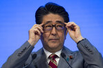 Shinzo Abe, Prime Minister of Japan, adjusts his glasses as he speaks during a plenary session in the Congress Hall at the 49th annual meeting of the World Economic Forum, WEF, in Davos, Switzerland, Wednesday, Jan. 23, 2019. T(Gian Ehrenzeller/Keystone via AP)
