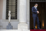 Greek Prime Minister Kyriakos Mitsotakis looks at his watch as he waits for the arrival of the head of the Presidential Council of Libya Mohamed al-Menfi prior their meeting, in Athens, on Wednesday, April 14, 2021.(AP Photo/Petros Giannakouris)