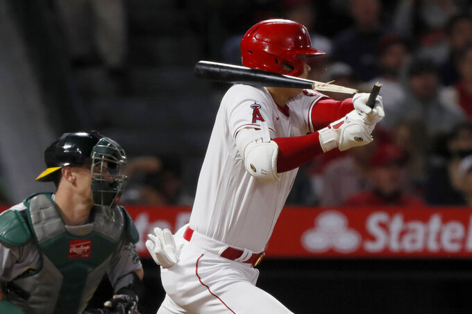 Los Angeles Angels designated hitter Shohei Ohtani hits a broken-bat single next to Oakland Athletics catcher Sean Murphy during the seventh inning of a baseball game in Anaheim, Calif., Saturday, Sept. 18, 2021. (AP Photo/Alex Gallardo)