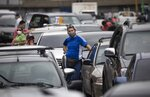 People stand outside their vehicles as they wait in a line near a gas station to fill their tanks in Caracas, Venezuela, Tuesday, Sept 8, 2020. Gasoline shortages have returned to Venezuela, sparking mile-long lines in the capital as international concerns mounted that Iran yet again may be trying to come to the South American nation's rescue. (AP Photo/Ariana Cubillos)
