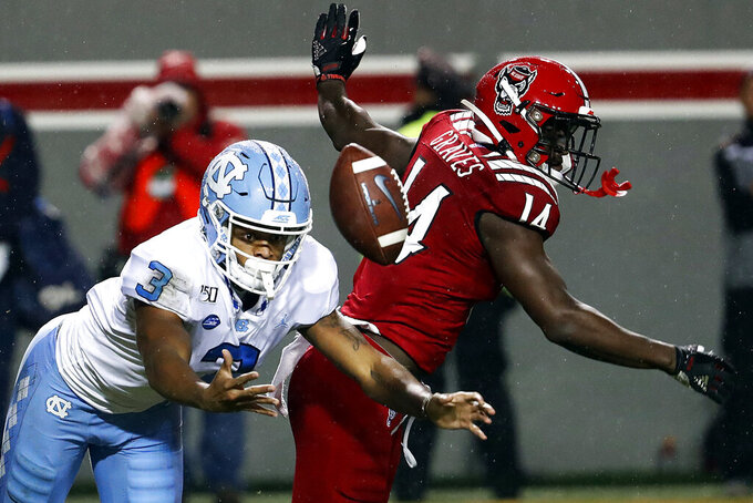 North Carolina State's De'Von Graves (14) breaks up a pass intended for North Carolina's Antoine Green (3) during the first half of an NCAA college football game in Raleigh, N.C., Saturday, Nov. 30, 2019. (AP Photo/Karl B DeBlaker)