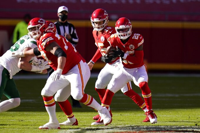 Kansas City Chiefs running back Le'Veon Bell (26) takes the hand off from quarterback Patrick Mahomes (15) and runs the ball for a first down in the second half of an NFL football game against the New York Jets on Sunday, Nov. 1, 2020, in Kansas City, Mo. (AP Photo/Jeff Roberson)
