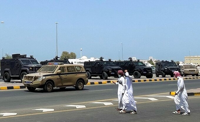 People walk near riot police cars in Sohar, Oman, Tuesday, May 25, 2021. On Tuesday, dozens of protesters angry over firings and the poor economy of Oman marched in Sohar, a city some 200 kilometers northwest of the capital, marking a third day of demonstrations in the typically subdued sultanate. (AP Photo)
