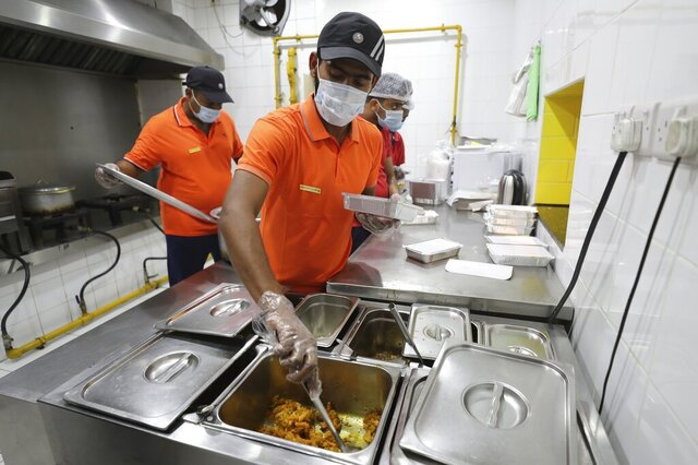 Cooks prepare free food for needy people at a restaurant in Sharjah, United Arab Emirates, Wednesday, Nov. 4, 2020. In this industrial underbelly in the suburbs of Dubai, workers methodically assemble packaged takeout meals of biryani rice, dal and brightly colored chicken curry for people in poverty and desperate to eat. (AP Photo/Kamran Jebreili)