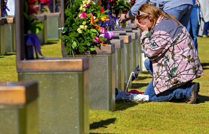 A person kneels at the memorial chair of Robbin Ann Huff and baby Amber Denise Huff in the Field of Chairs during the 26th Anniversary Remembrance Ceremony at the Oklahoma City National Memorial and Museum in Oklahoma City, Okla on Monday, April 19, 2021. (Chris Landsberger/The Oklahoman via AP)