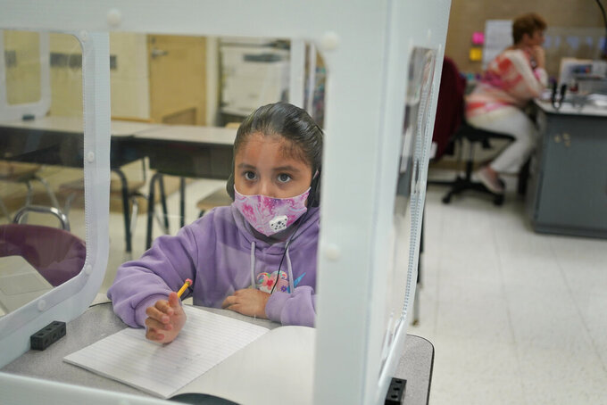 Second grader Abigail Meza does her school work at Christa McAuliffe School in Jersey City, N.J., Thursday, April 29, 2021. Kindergarten through third grade students are returning to their school buildings in Jersey City for their first time in over a year. New Jersey's two largest cities have begun making their return to classrooms in person after working remotely because of the COVID-19 outbreak. Students in Jersey City began returning to school today, just days after Newark officials said they were expanding in-person instruction to four days a week, up from two. (AP Photo/Seth Wenig)