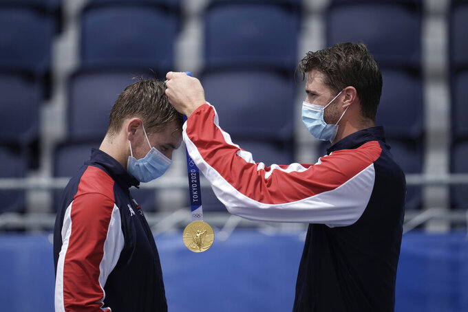 Anders Berntsen Mol, right, of Norway, puts the gold medal on teammate Christian Sandlie Sorum, as they celebrate a men's beach volleyball Gold Medal during a ceremony at the 2020 Summer Olympics, Saturday, Aug. 7, 2021, in Tokyo, Japan. (AP Photo/Felipe Dana)