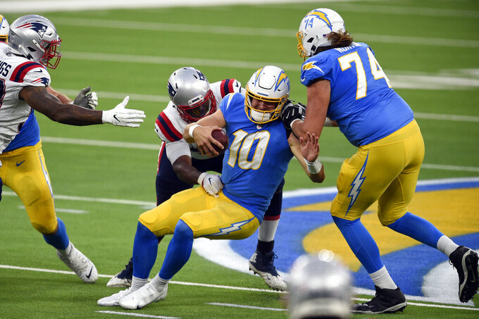Los Angeles Chargers quarterback Justin Herbert (10) is sacked by New England Patriots defensive tackle Adam Butler during the second half of an NFL football game Sunday, Dec. 6, 2020, in Inglewood, Calif. (AP Photo/Kelvin Kuo)