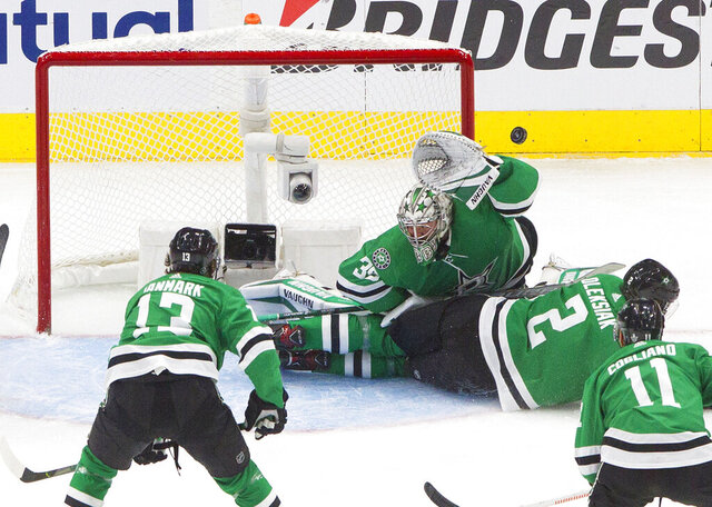 Dallas Stars goalie Anton Khudobin (35) makes a save against the Vegas Golden Knights as Stars defenseman Jamie Oleksiak (2) slides into the crease during second-period NHL Western Conference final playoff game action in Edmonton, Alberta, Saturday, Sept. 12, 2020. (Jason Franson/The Canadian Press via AP)