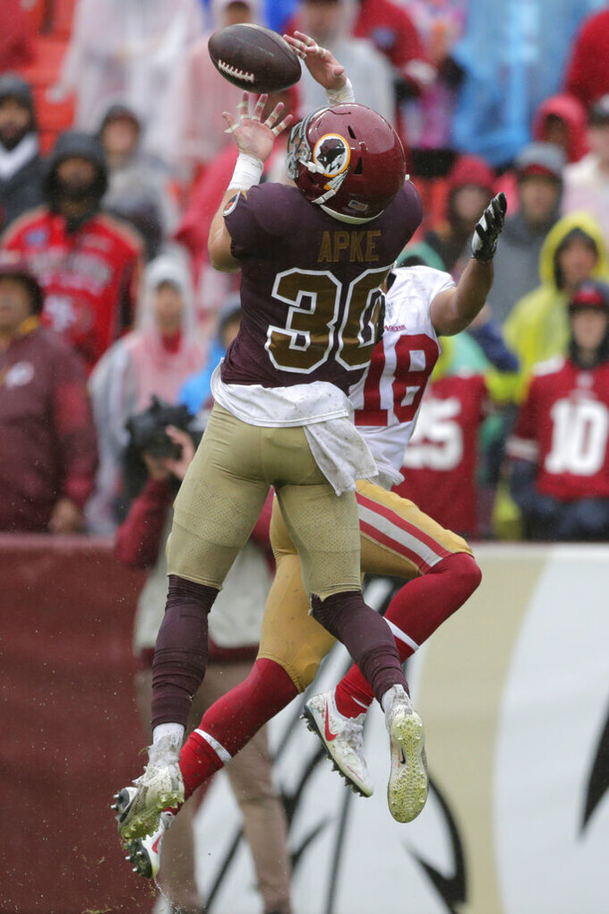 Washington Redskins defensive back Troy Apke, left, intercepts a pass attempt intended for San Francisco 49ers wide receiver Dante Pettis in the second half of an NFL football game, Sunday, Oct. 20, 2019, in Landover, Md. (AP Photo/Julio Cortez)