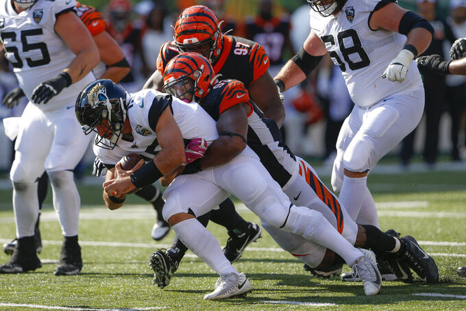 Jacksonville Jaguars quarterback Gardner Minshew, left, is tackled by Cincinnati Bengals defensive tackle Andrew Brown (93) in the second half of an NFL football game, Sunday, Oct. 20, 2019, in Cincinnati. (AP Photo/Gary Landers)