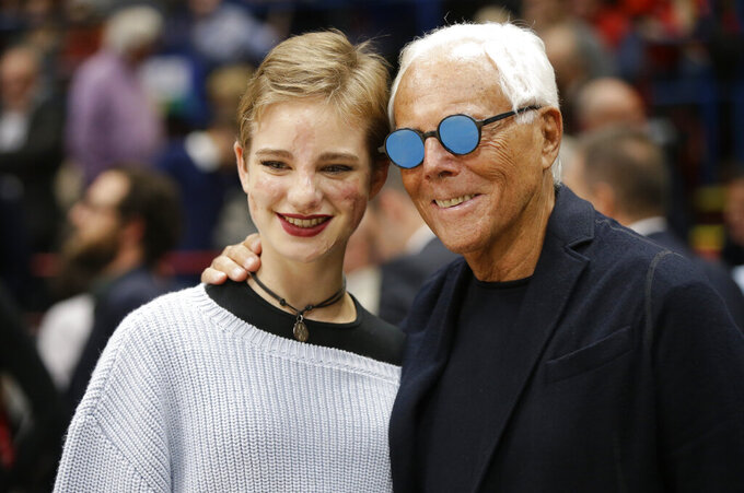 """FILE - In this Oct. 27, 2016, file photo, Giorgio Armani and paralympic champion Beatrice 'Bebe' Vio pose during a Euroleague basketball match between EA7 Emporio Armani Milan and Real Madrid in Assago, near Milan, Italy. Vio is among several Paralympic athletes who are profiled in the Nexflix documentary """"Rising Phoenix"""" that will be released in 190 countries on Wednesday, Aug. 26, 2020.(AP Photo/Luca Bruno, File)"""