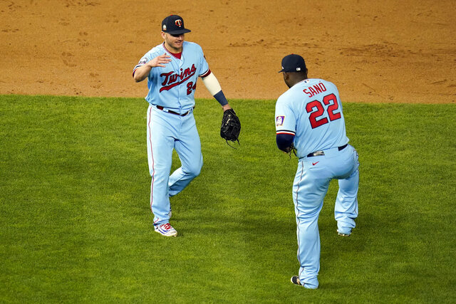 Minnesota Twins' Josh Donaldson, left, and Miguel Sano celebrate the Twins' 8-1 win over the Chicago White Sox in a baseball game Wednesday, Sept. 2, 2020, in Minneapolis. (AP Photo/Jim Mone)