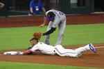 Texas Rangers' Jeff Mathis, bottom, slides into third ahead of the tag by Colorado Rockies third baseman Nolan Arenado (28) in the third inning of a baseball game Saturday, July 25, 2020, in Arlington, Texas. (AP Photo/Richard W. Rodriguez)