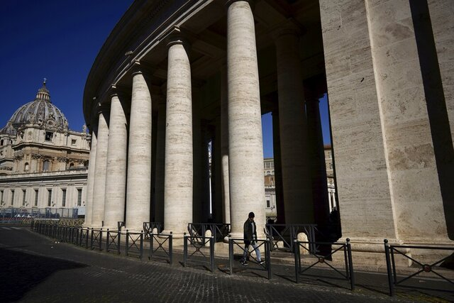 A man walks by Bernini's colonnade in St. Peter's Square during Pope Francis' weekly general audience, streamed by the Vatican television due to restrictions to contain the Covid-19 virus, at the Vatican, Wednesday, April 1, 2020. The new coronavirus causes mild or moderate symptoms for most people, but for some, especially older adults and people with existing health problems, it can cause more severe illness or death. (AP Photo/Andrew Medichini)