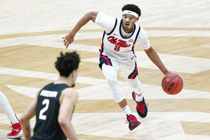 Mississippi's Devontae Shuler, right, moves the ball against South Carolina in the first half of an NCAA college basketball game in the Southeastern Conference Tournament Thursday, March 11, 2021, in Nashville, Tenn. (AP Photo/Mark Humphrey)