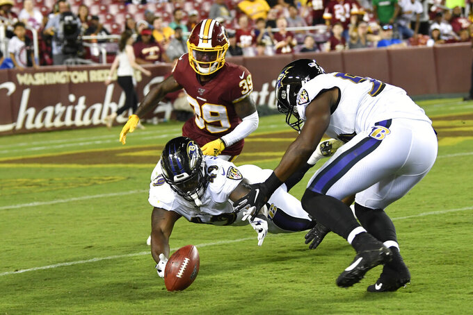 Baltimore Ravens fullback Christopher Ezeala (49) reaches out to recover the ball after a blocked punt during the second half of an NFL preseason football game against the Washington Redskins at FedEx Field in Landover, Md., Thursday, Aug. 29, 2019. Ravens linebacker Silas Stewart, right, tries to help as Redskins defensive back Jeremy Reaves (39) watches. (AP Photo/Susan Walsh)