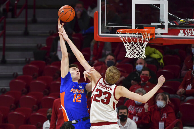 Florida forward Colin Castleton (12) has his shot blocked by Arkansas forward Connor Vanover (23) during the first half of an NCAA college basketball game in Fayetteville, Ark. Tuesday, Feb. 16, 2021. (AP Photo/Michael Woods)