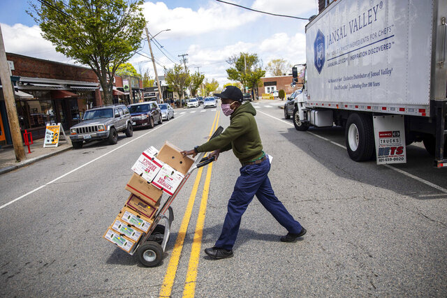 Gibson Mbedzi delivers vegetables to a restaurant opening for take out, Saturday, May 9, 2020, in Providence, R.I. Non-essential businesses are reopening under Gov. Gina Raimondo's plan to gradually lift some restrictions imposed to slow the outbreak. Face masks are now required for anyone in a public place and bars, salons and gyms remain closed while restaurants remain limited to take out and delivery. (AP Photo/David Goldman)