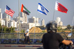 A woman wearing a face mask against the coronavirus pandemic walks past American, United Arab Emirates, Israel and Bahraini flags at the Peace Bridge in Netanya, Israel, Monday, Sept. 14, 2020. For the first time in more than a quarter-century, a U.S. president will host a signing ceremony between Israelis and Arabs at the White House, billing it as an