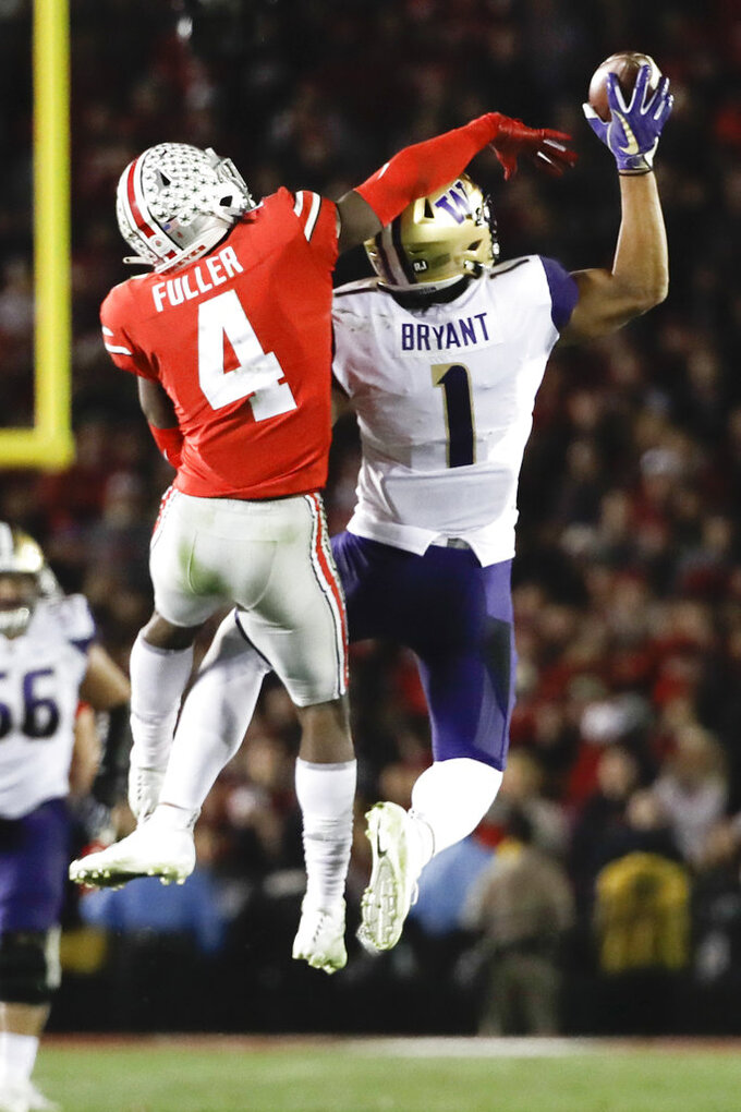 Washington tight end Hunter Bryant, right, catches a pass next to Ohio State safety Jordan Fuller during the second half of the Rose Bowl NCAA college football game Tuesday, Jan. 1, 2019, in Pasadena, Calif. (AP Photo/Jae C. Hong)