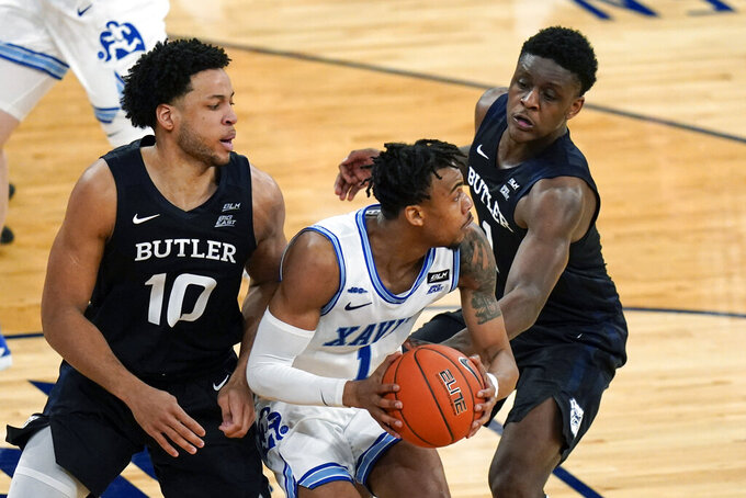 Butler's Bryce Nze (10) and Bo Hodges (1) defend Xavier's Paul Scruggs (1) during the overtime period of an NCAA college basketball game in the Big East conference tournament Wednesday, March 10, 2021, in New York. (AP Photo/Frank Franklin II)