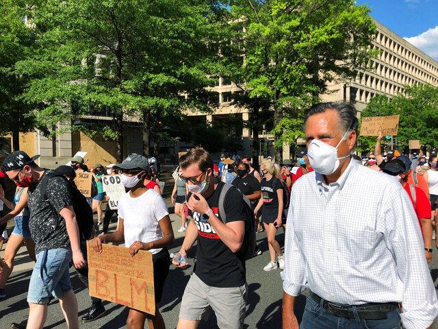 Sen. Mitt Romney, R-Utah, marches with a crowd singing