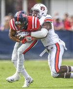 Mississippi wide receiver DaMarkus Lodge (5) is tackled by Auburn defensive back Daniel Thomas (24) during an NCAA college football game at Vaught-Hemingway Stadium in Oxford, Miss., Saturday, Oct. 20, 2018. (Bruce Newman/The Oxford Eagle via AP)