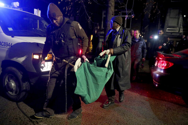 A Chicago police officer and a Chicago Animal Care and Control worker carry a coyote out in a green bag after tranquilizing the animal behind a home on Thursday, Jan. 9, 2020.   Authorities on the hunt for coyotes in downtown Chicago after two reported attacks, including one where passersby said they had to pull a wild canine off of a 6-year-old boy who was bitten in the head, captured one animal Thursday night on the city's North Side.(Chris Sweda/Chicago Tribune via AP)