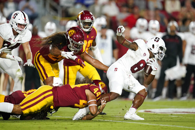 Stanford running back Nathaniel Peat (8) is tackled by Southern California linebacker Tuasivi Nomura (44) during the first half of an NCAA college football game Saturday, Sept. 11, 2021, in Los Angeles. (AP Photo/Marcio Jose Sanchez)