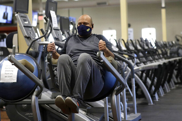 Earl Edwards, of Canton, Mass., works out on a piece of exercise equipment, Monday, July 6, 2020, at Answer is Fitness gym, in Canton. Casinos, gyms, movie theaters, and museums are among the businesses allowed to reopen in the state on Monday, under the third phase of Massachusetts Gov. Charlie Baker's coronavirus economic recovery plan. The rules don't apply to Boston, which is to move into phase three on July 13. (AP Photo/Steven Senne)