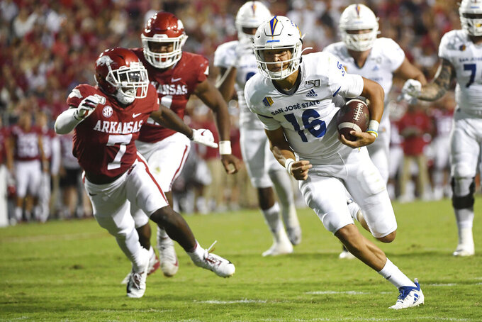 San Jose State quarterback Nick Nash gets past Arkansas defender Joe Foucha to score a touchdown during the first half of an NCAA college football game, Saturday, Sept. 21, 2019,in Fayetteville, Ark. (AP Photo/Michael Woods)