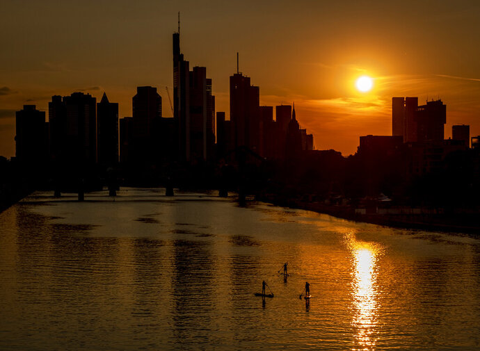 Three stand up paddlers on the river Main in Frankfurt, Germany, as the sun sets, Tuesday, Aug. 4, 2020. (AP Photo/Michael Probst)