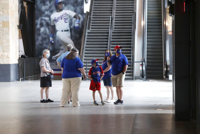 "Baseball fans check out the concourse at Globe Life Field, the new home of the Texas Rangers baseball team,  during the first day of public tours Monday, June 1, 2020, in Arlington, Texas. As lock-downs are lifted, restrictions on social gatherings eased and life begins to resemble some sense, sports are finally starting to emerge from the coronavirus pandemic. Major League Soccer, the NBA and NHL have agreements in place to restart their seasons, and baseball is going through contentious rounds of negotiations over what it might take for umpires to cry ""Play Ball!"" and America's pastime to provide a weary public some much-needed entertainment.(AP Photo/LM Otero, File)"