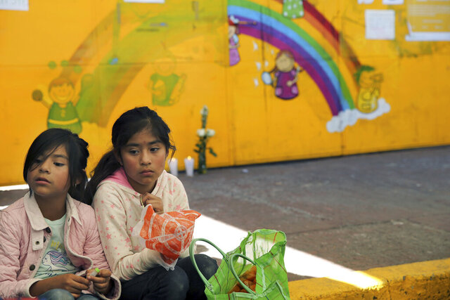 Classmates of Fatima, a 7-year-old girl who was abducted from the entrance of the Enrique C. Rebsamen primary school and later murdered, sit in front of the school entrance in Mexico City, Monday, Feb. 17, 2020. The girl's body was found wrapped in a bag and abandoned in a rural area on Saturday and was identified by genetic testing. (AP Photo/Marco Ugarte)