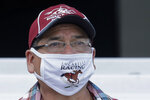 Salvador Hernandez, a groom at Emerald Downs Racetrack in Auburn, Wash., wears a mask as he watches a race Wednesday, June 24, 2020, on the first day of thoroughbred horse racing at the track since all professional sports in Washington state were curtailed in March by the outbreak of the coronavirus. No spectators were allowed, but online wagering was available and the races were streamed. Organizers hope to continue racing into October on a modified schedule. (AP Photo/Ted S. Warren)