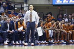 Texas coach Shaka Smart reacts during the first half of an NCAA college basketball game against West Virginia Monday, Jan. 20, 2020, in Morgantown, W.Va. (AP Photo/Kathleen Batten)