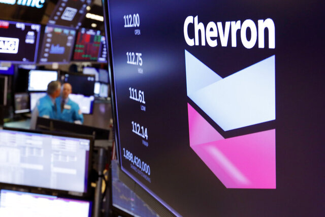 FILE - This Oct. 8, 2019, file photo shows the logo for Chevron on the floor of the New York Stock Exchange. Chevron Corp. reports financial results Friday, Nov. 1. Chevron said Tuesday, Dec. 10, it will book a charge of at least $10 billion because lower long-term prices for oil and natural gas are making some projects less valuable.  (AP Photo/Richard Drew, File)