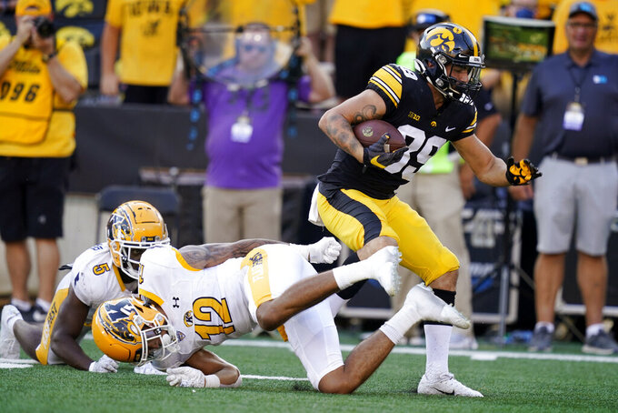 Iowa wide receiver Nico Ragaini (89) breaks a tackle by Kent State cornerback Capone Blue (12) after catching a pass during the second half of an NCAA college football game, Saturday, Sept. 18, 2021, in Iowa City, Iowa. Iowa won 30-7. (AP Photo/Charlie Neibergall)
