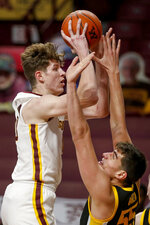 Minnesota center Liam Robbins shoots over Iowa center Luka Garza (55) during the first half of an NCAA college basketball game Friday, Dec. 25, 2020, in Minneapolis. (AP Photo/Bruce Kluckhohn)